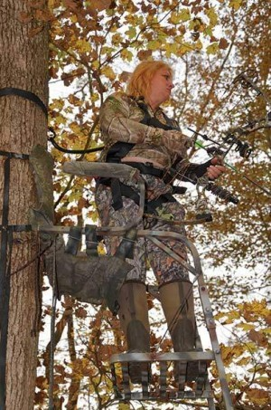 Joella Bates, a world champion archer prepares to take a shot at a deer while hunting from a traditional tree stand.